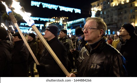 men hold burning torches. Ukrainian nationalists torchlight procession (torch march) in honor of the 111th anniversary of the birth of Stepan Bandera. January 1, 2020 Kyiv, Ukraine