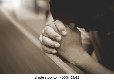 Men hold hands and pray to God in the church.