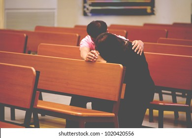 Men  hold hands with women , pray for God in church.