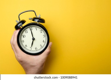 men holding black alarm clock in one hand on yellow background color