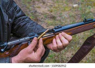Men holding the bullet to loading his carbine close up outdoors