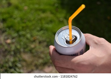 Men holding can with yellow drinking straw on blurred green grass background