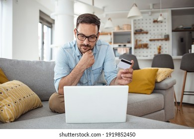 Men holding credit card and using laptop at home office. Young adult male making online purchase. Online shopping. Young handsome man shopping online with credit card and laptop at home