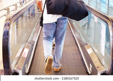 Men at horizontal escalator covered. Moving walkway, moving sidewalk, moving pavement, autopedescalator, walkalator, travelator, autowalk, horizontal escalator, slidewalk, or moveator at an airport.