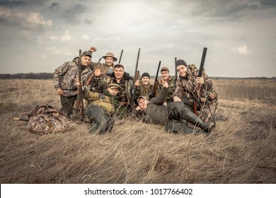 Men hunters group team portrait in rural field posing together against overcast sky during hunting season. Concept for teamwork.