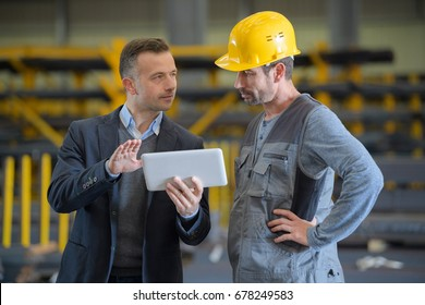 Men in industrial building looking at tablet