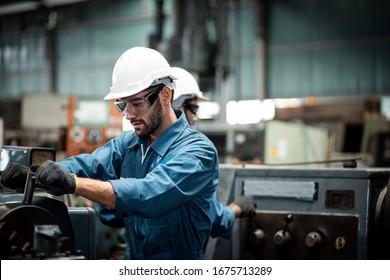 Ein männlicher Industrietechniker trägt einen weißen Helm, während er in einer schweren Fabrik hinter sich steht. Die Instandhaltung der Arbeit an Industriemaschinen und die Kontrolle der Sicherheit in der Fabrik.