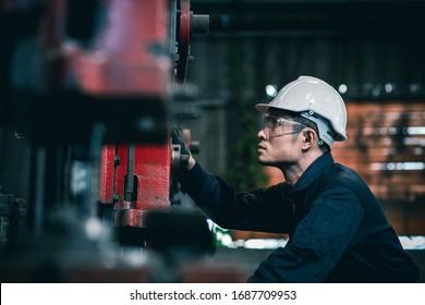 Ein männlicher Industrietechniker trägt einen weißen Helm, während er in einer schweren Fabrik hinter sich steht. Die Instandhaltung der Arbeit an Industriemaschinen und die Kontrolle der Einrichtung des Sicherheitssystems in der Tat
