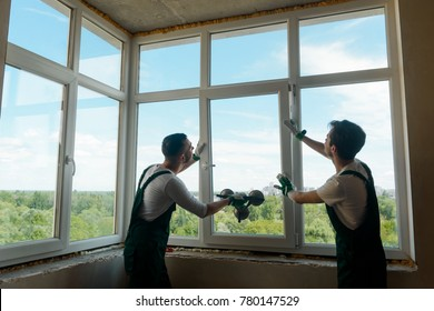Men are installing a window. Two development company employee works inside of new apartment