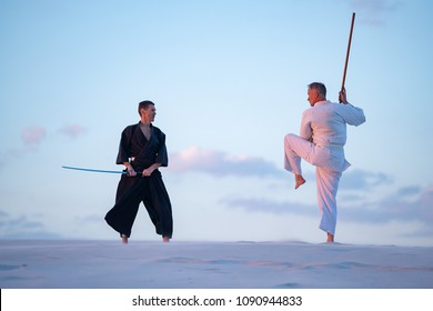 Men, in Japanese clothes, are practicing martial arts with a traditional Japanese weapon - a katana and jo in the desert in the pink rays of the setting sun.