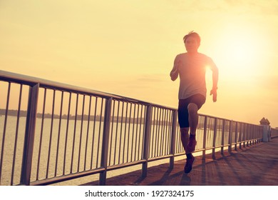 Men jogging in the evening on the bridge over the river.