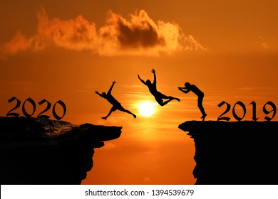 Men are jumped between high cliff at a red sky sunset background, Silhouette concept of new year 2020,