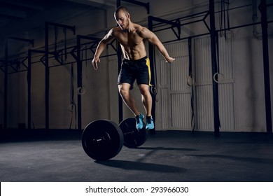 Men jumping over barbells during burpees exercise