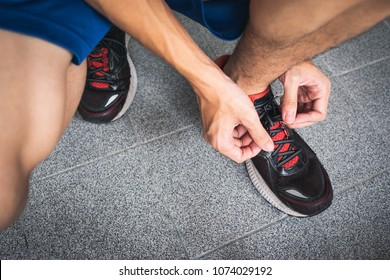 Men lacing up running shoes