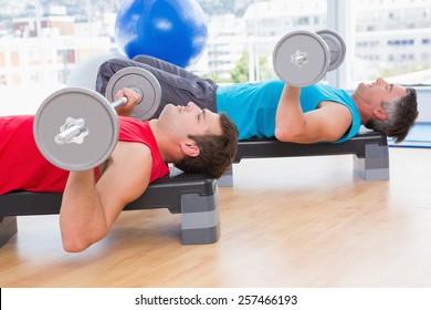Men lifting barbell in fitness studio