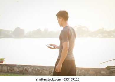 Men listen to music with the phone,Man using his Mobile Phone outdoor, close up.