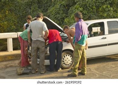 Men looking under the hood and repairing broken down Fiat car in the Valle de Vinales, in central Cuba