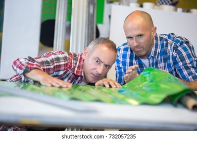 men looking at unrolled green plastic material