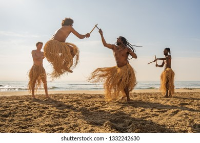 Men in maculele skirt practicing capoeira (brazilian martial art that combines elements of dance, acrobatics and music) on the beach