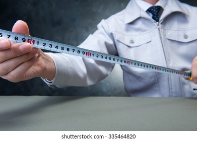 Men measure the length with a ruler