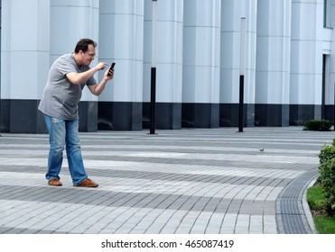 Men with a mobile phone in front of a white business center looking for something in it