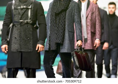 Men models walk the runway during a Fashion Show. Fashion catwalk event showing new collection of clothes. Holding expensive brown bag.