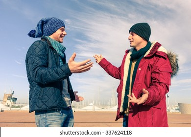 Men models wearing winter clothes using gesturing in friendly discussion - Best male friends are hugging - Trendy students having fun outdoor in sunny day - Concept of friendship happiness and youth