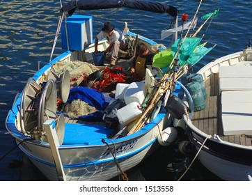 Men on a fishing boat in the harbour of Saint Tropez, the ritzy French Riviera seaside resort.