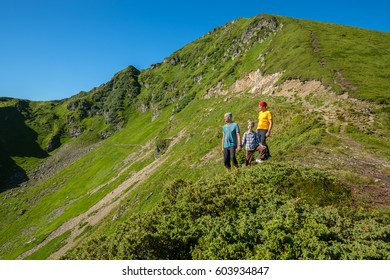 Men on travel. Happy men and boy stand on the cliff among the mountain slopes covered with green grass, enjoying the view of the mountains on a beautiful sunny day.