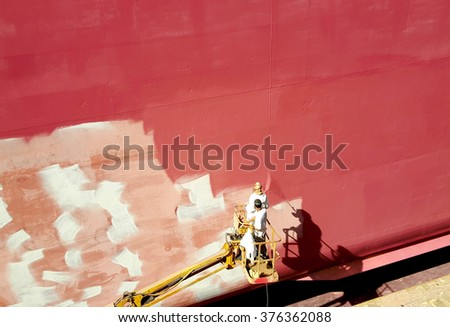 men painting ship hull