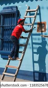 a men painting in the village of choroni on the caribbean coast in Venezuela.   Venezuela, Choroni, November, 2005