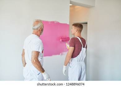 Men Painting The Wall With Paint Roller