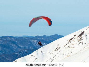 Men paragliding at winter snowy mountains background. Extreme sport