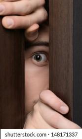Men peeking. Close-up of men peeking through the open door