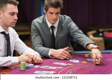 Men placing bets at poker game in casino