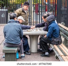 Men play mahjong in New York City Chinatown park on Nov 5, 2011