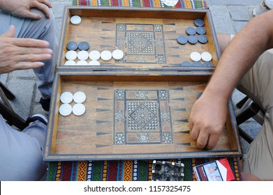 Men playing backgammon board game with an old wooden table, checkers and dice in Turkey