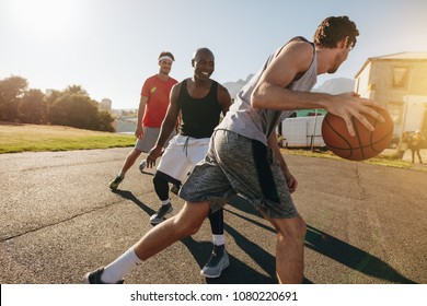 Men playing basketball game on a sunny day. Men practicing basketball skills in play area.