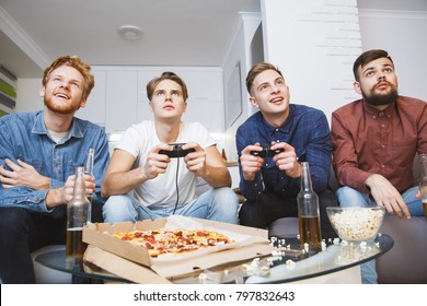 Men playing soccer on game console together at home