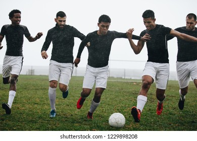 Men playing soccer running after a football on a rainy morning. Footballers trying to take possession of the ball running on the field playing soccer.