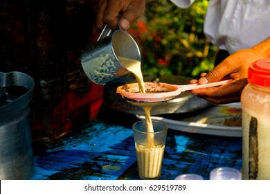 men pouring cup hot tea indian style or chai for customers from his shop along street