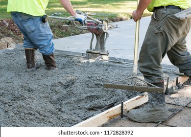 Men Pouring and Finishing a Concrete Slab Driveway with a Wet Cement Mix