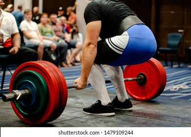men powerlifter deadlift competition in sport gym with fans