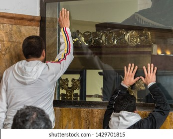 """Men are praying in sanctuary """"El Senor Caido"""" from the 17th century on the Monserrate hill in Bogota,  Sanctuary of Christ falling under the cross, Colombia, South America"""