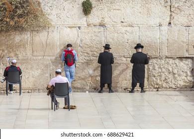 men praying at the wailing wall, jerusalem, israel