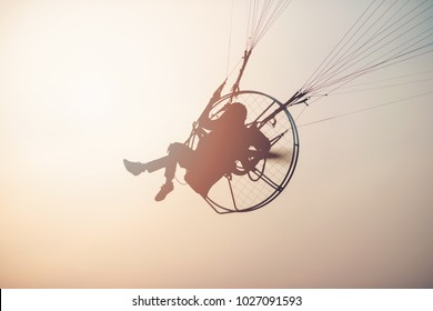 Men are preparing to fly by paramotor.