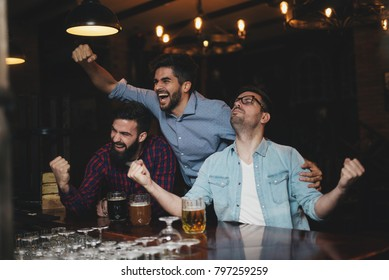 Men at the pub watching game and drinking beer. They are having good time.