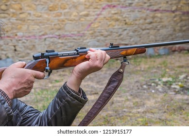 Men pulling the trigger of hunting carbine