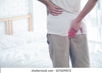 Men put their hands on the buttocks. Have anal pain.The man stands in a white room. Handles the buttocks for abdominal pain.