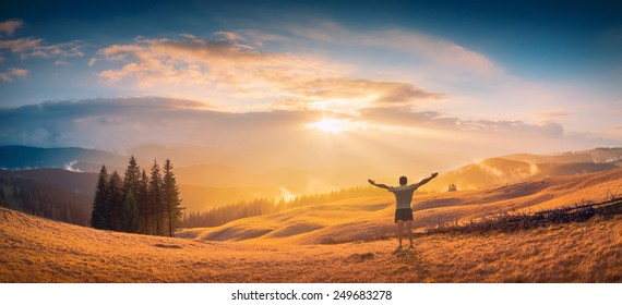 Men with raised hands, who welcome golden sunrise in a Carpathian foggy valley and enjoying landscape.